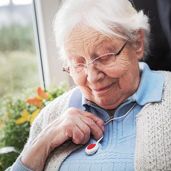 Seniorin überprüft ihren Hausnotrufknopf.