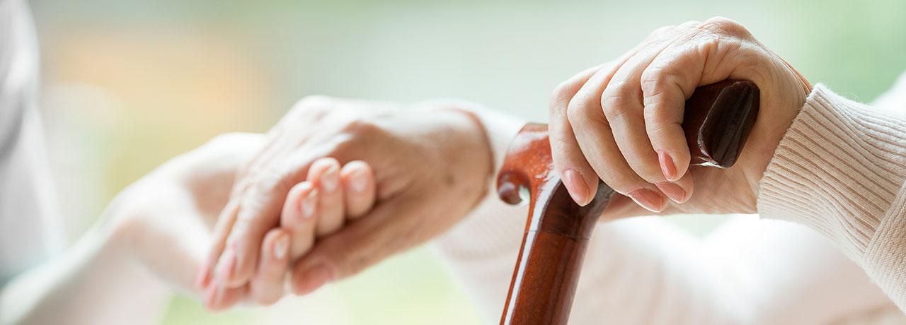 helfende hände unterstützen eine ältere dame am gehstock