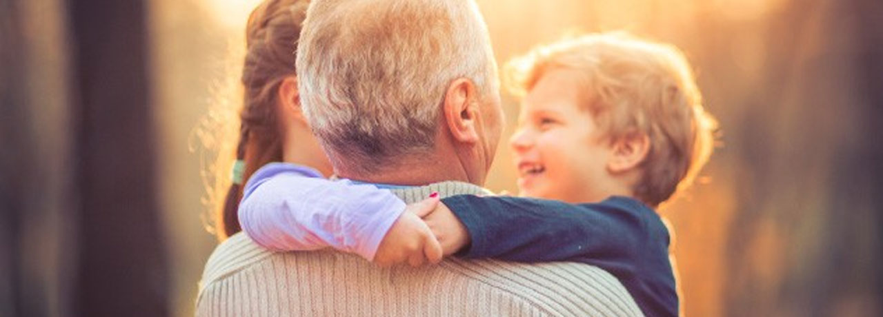Opa hält seine beiden Enkelkinder auf dem Arm.