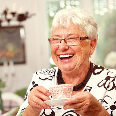 Seniorin hat eine Kaffee-Tasse in der Hand und lacht dabei.