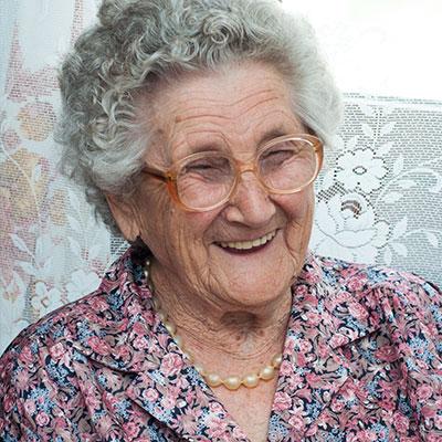 Seniorin mit Brille lächelt in die Kamera.