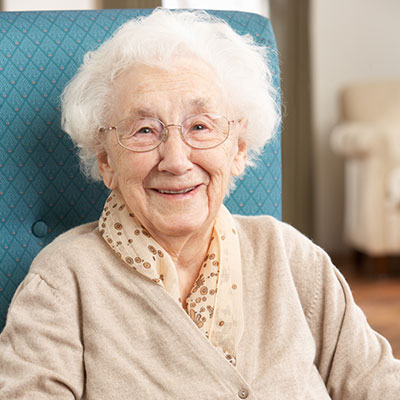 Seniorin sitzt auf ihrem blauen Sessel.