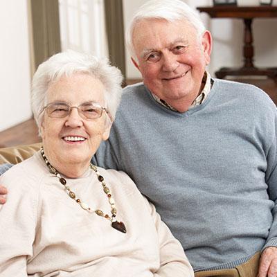 Ein Seniorenpaar sitzt zusammen auf der Couch.