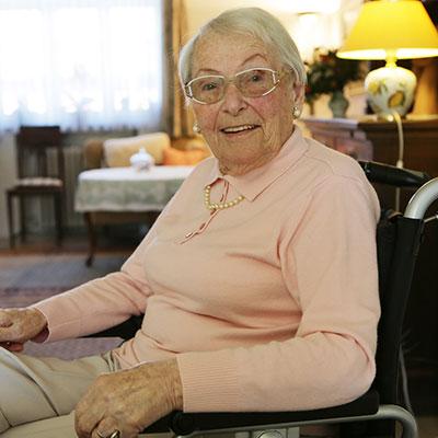 ältere Dame sitzt im Wohnzimmer auf einem Rollstuhl.