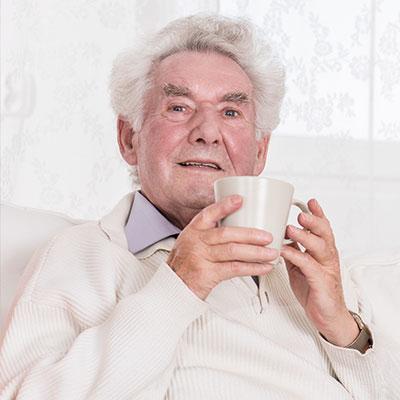 Senior sitzt in einem Sessel und hält eine Tasse vor sich.