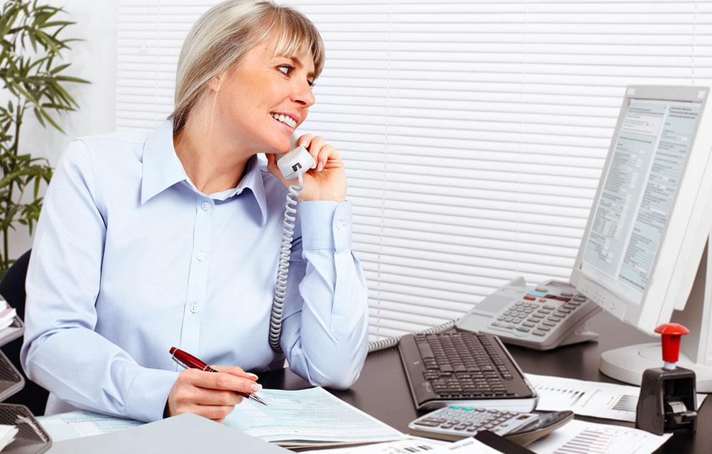 Mitarbeiterin sitzt in einem Büro und telefoniert, während sie etwas notiert.