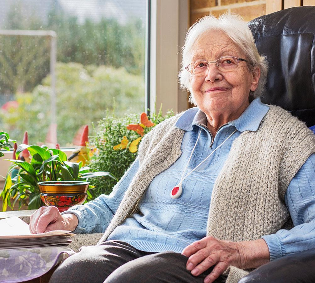 Seniorin mit Notruf sitzt in einem Sessel im Wohnzimmer.