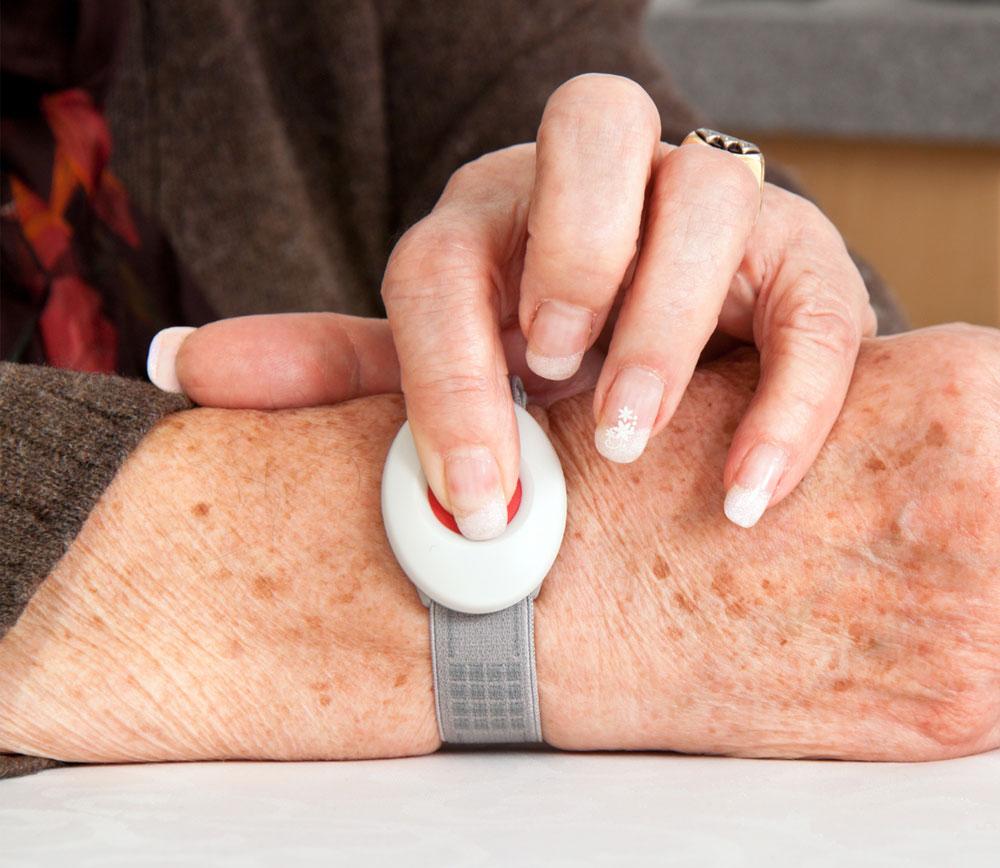 Notrufknopf am Arm einer älteren Dame wird von ihr gedrückt.