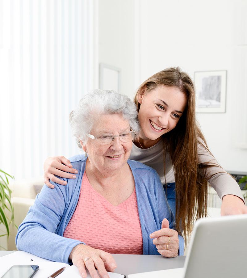 Enkelin unterstützt ihre Oma beim Internet.